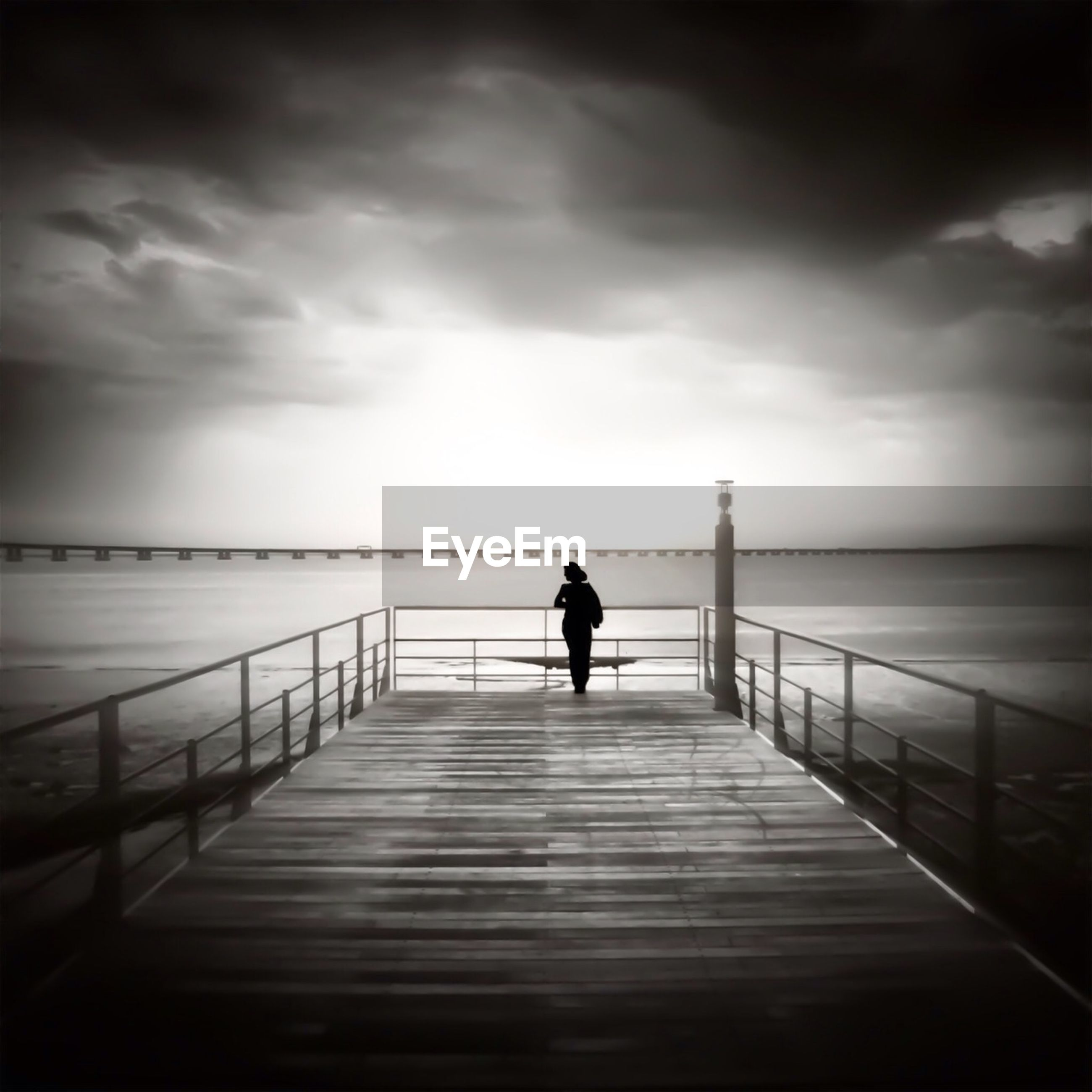 Silhouette woman on pier against cloudy sky at dusk