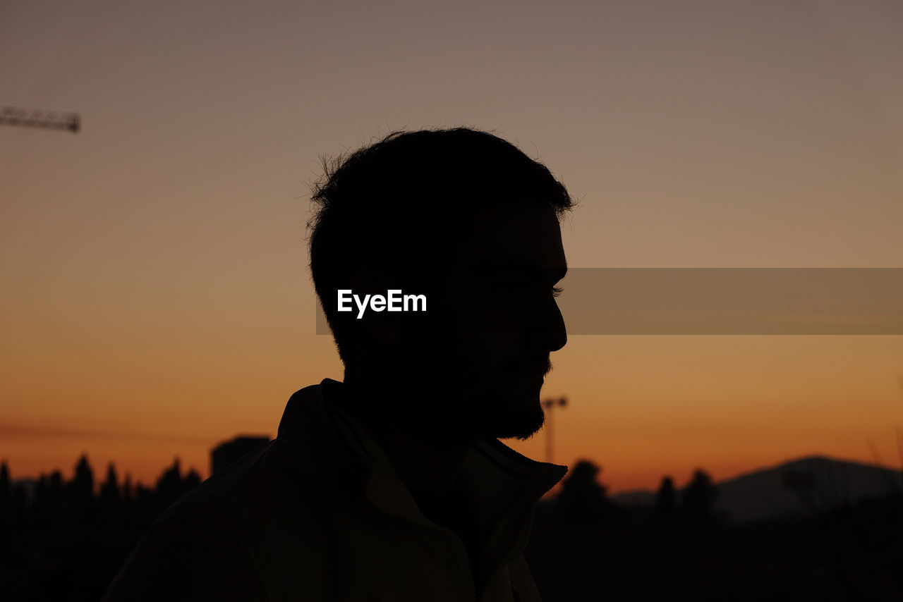 CLOSE-UP OF SILHOUETTE MAN AGAINST SUNSET SKY