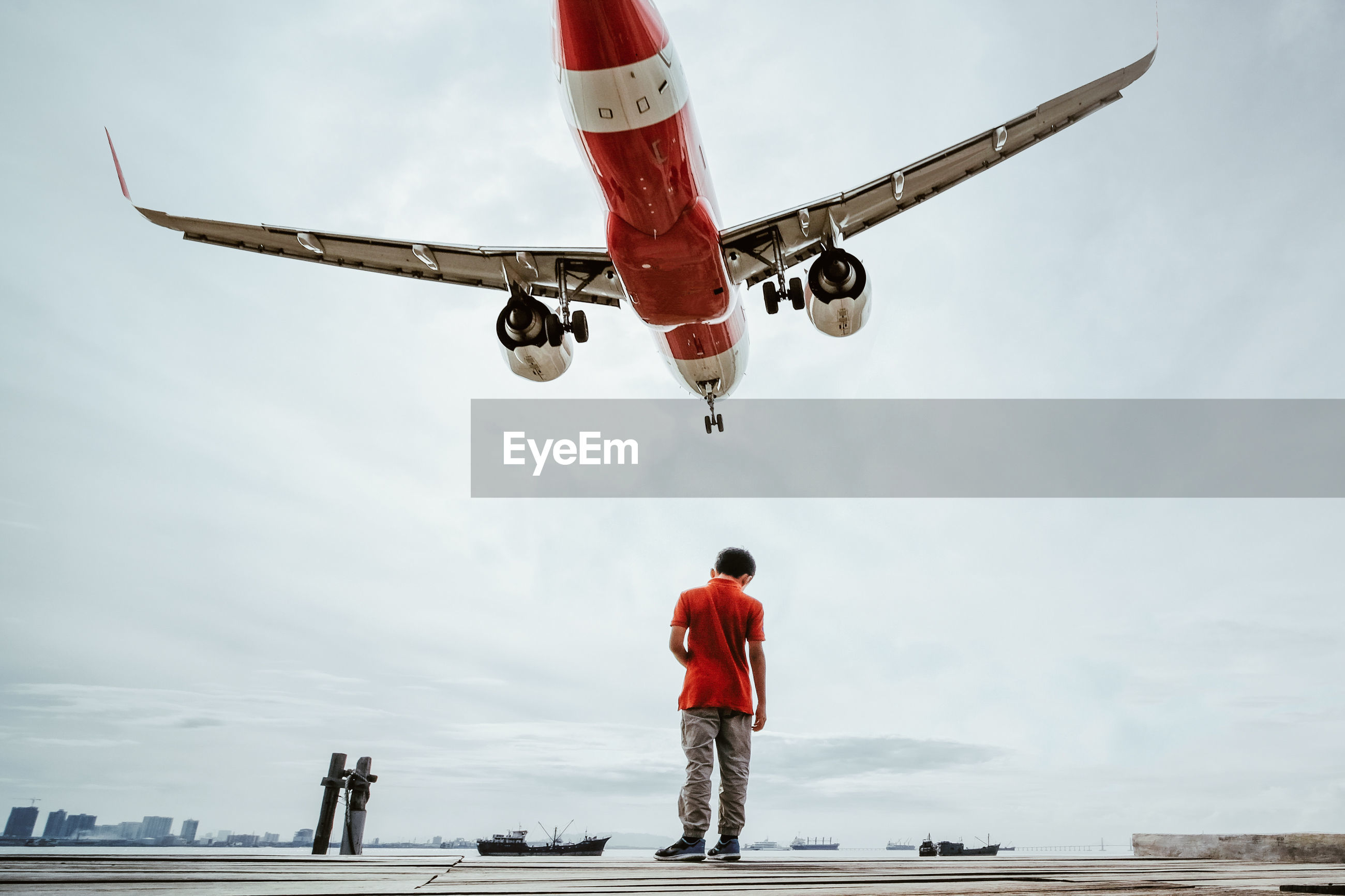 Rear view of boy standing on pier against airplane flying in sky