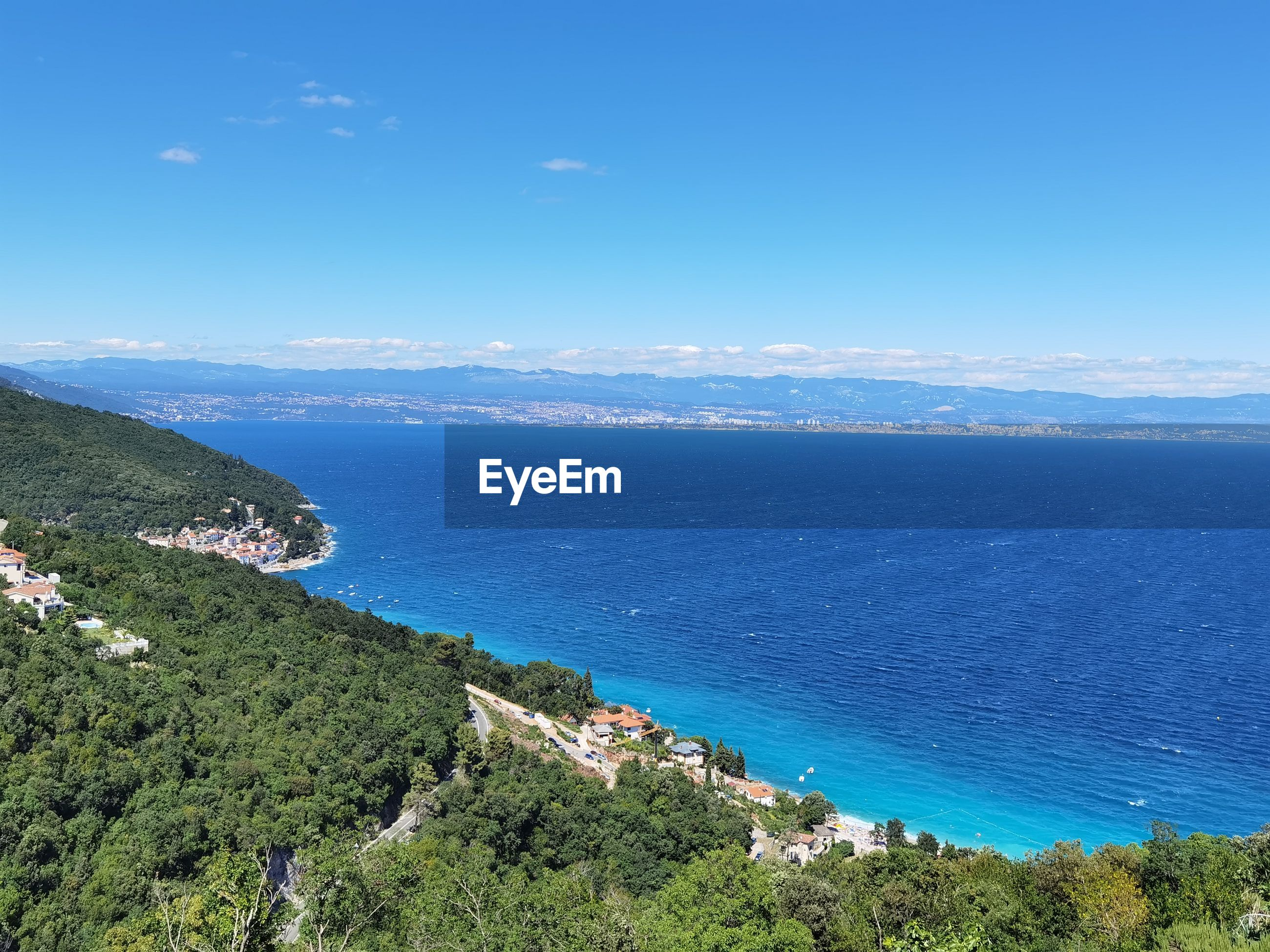 HIGH ANGLE VIEW OF SEA AND TREES AGAINST BLUE SKY