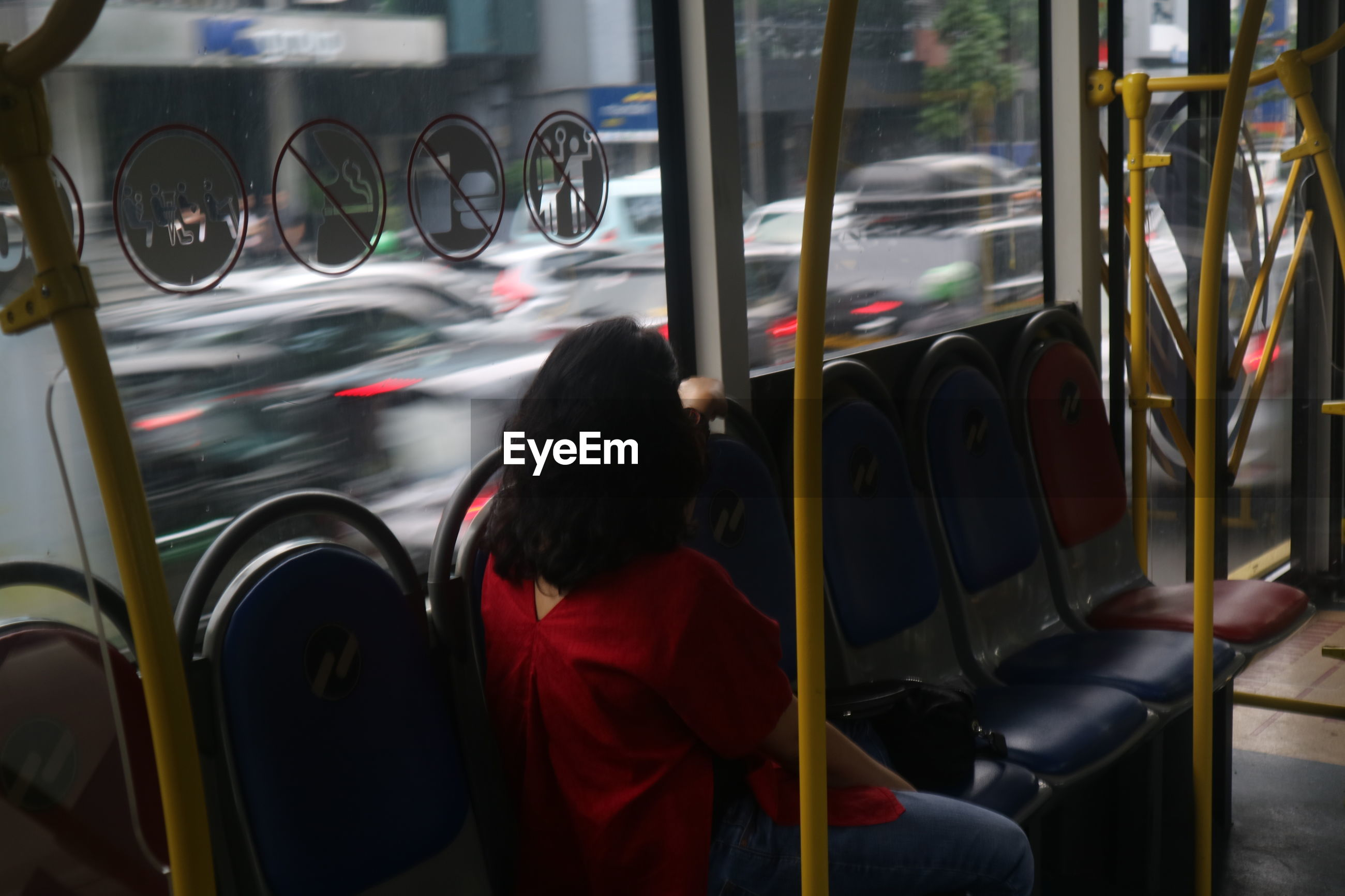 Woman looking through window while traveling by public transportation in city