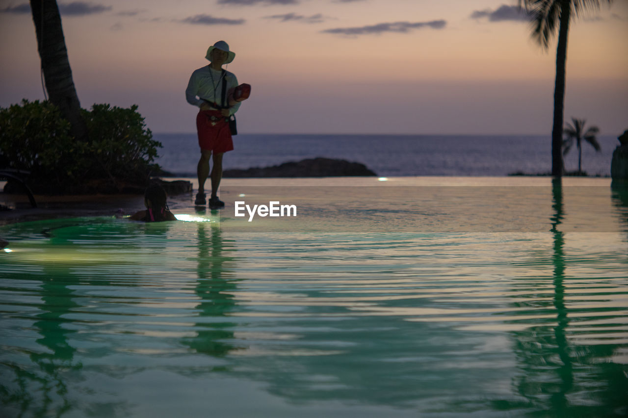 water, sea, real people, reflection, full length, one person, rear view, nature, scenics, sunset, men, outdoors, beauty in nature, silhouette, lifestyles, standing, horizon over water, sky, day, people
