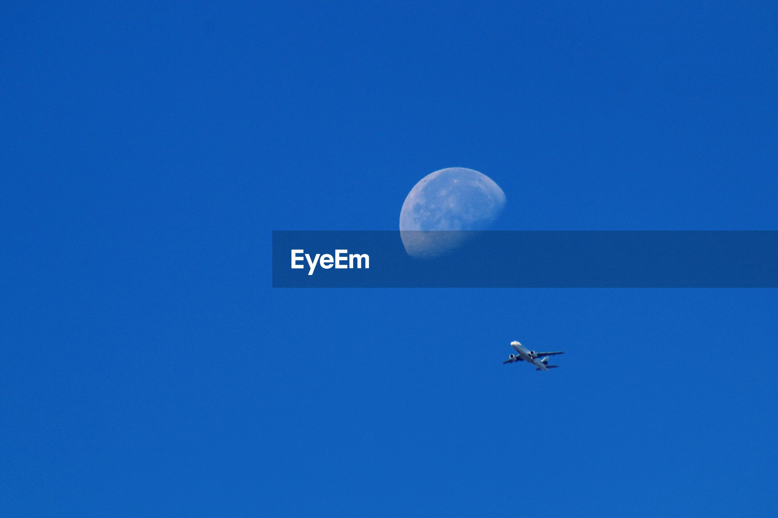 Low angle view of airplane flying with moon in background