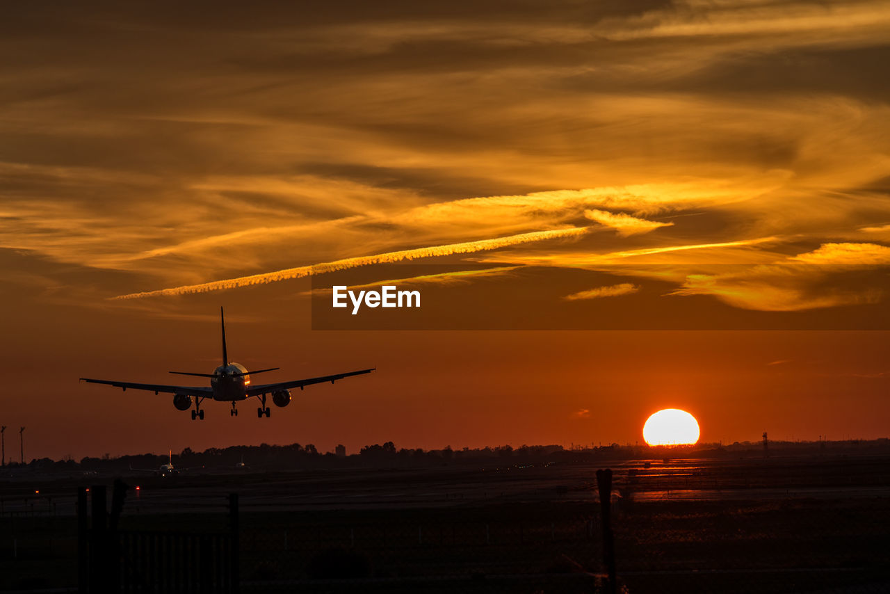 Airplane taking off against sky during sunset