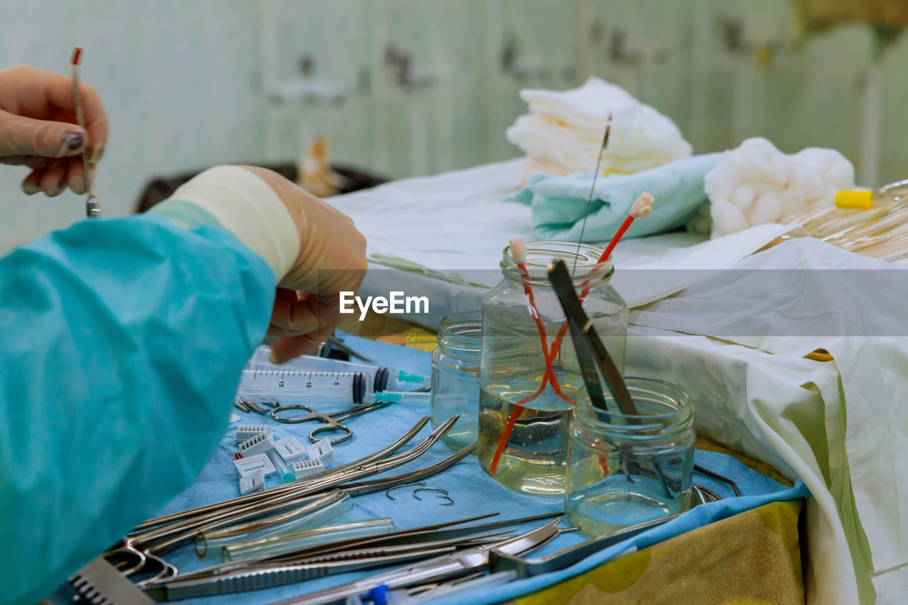 Midsection of surgeon holding surgical equipment