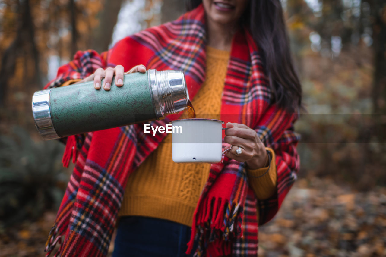 Midsection Of Woman Pouring Drink From Insulated Drink Container In Forest
