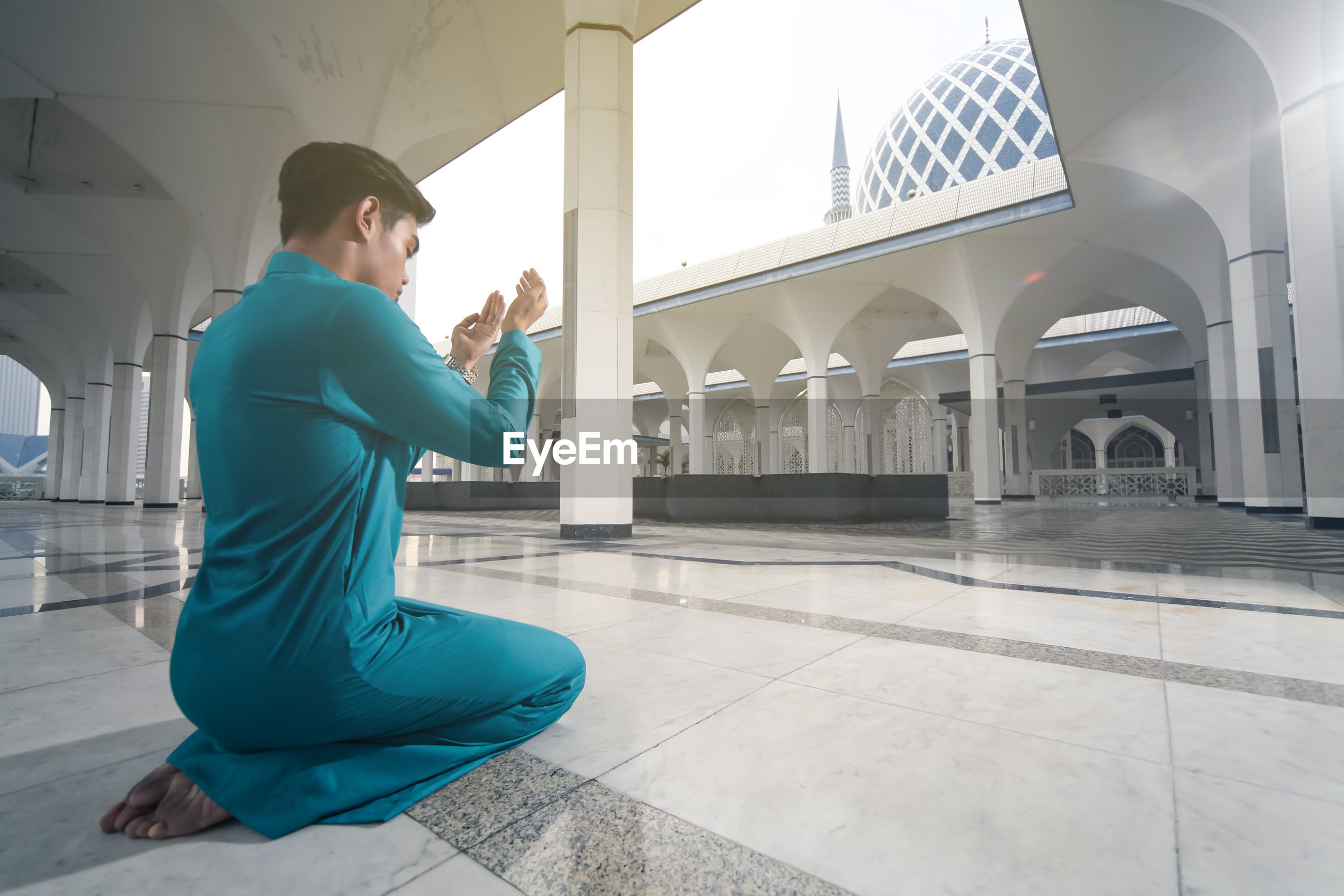 Rear view of man standing in mosque