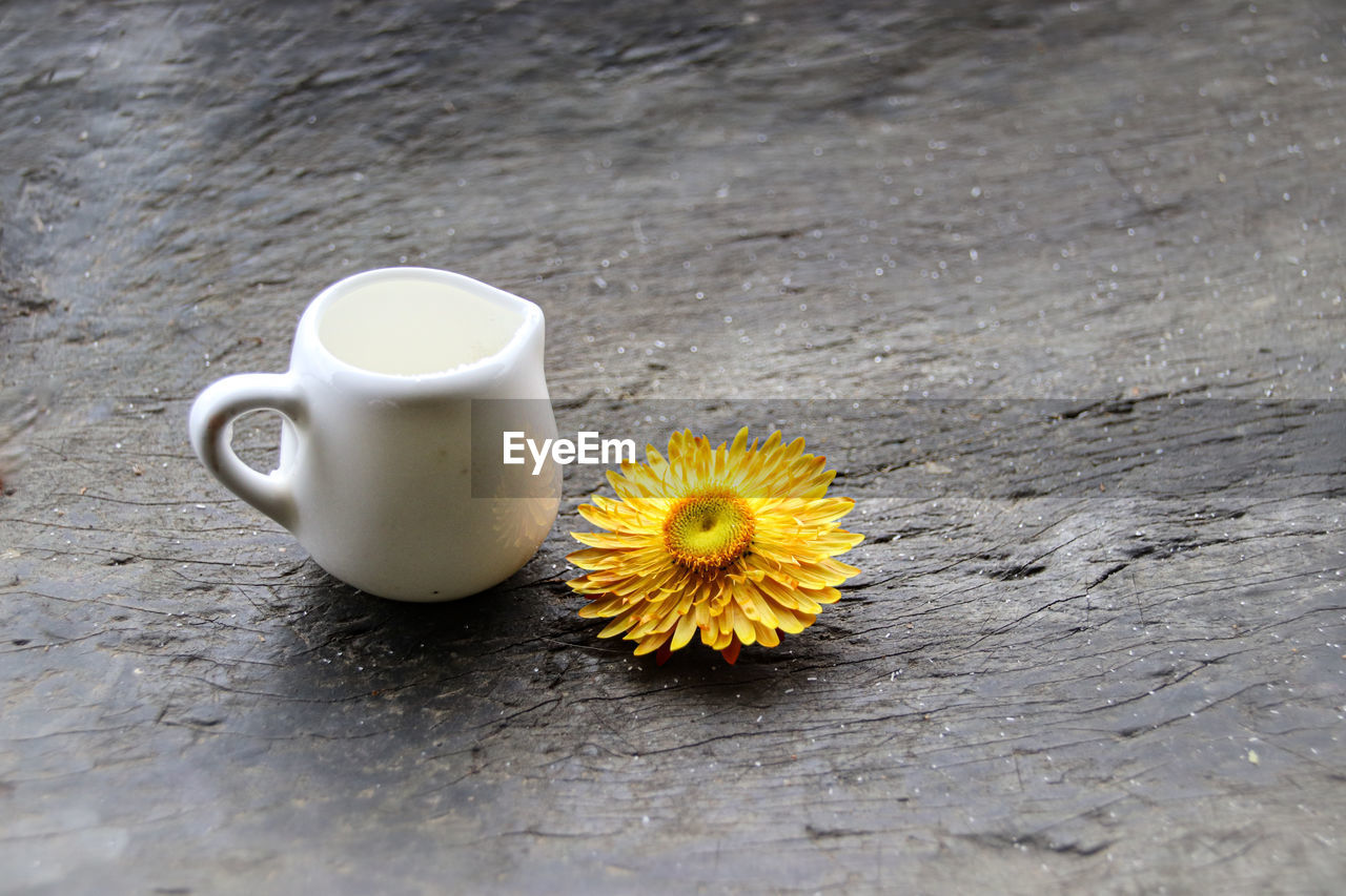 cup, freshness, food and drink, flower, yellow, flowering plant, drink, table, mug, refreshment, coffee cup, wood - material, still life, close-up, no people, high angle view, coffee, coffee - drink, white color, plant, flower head