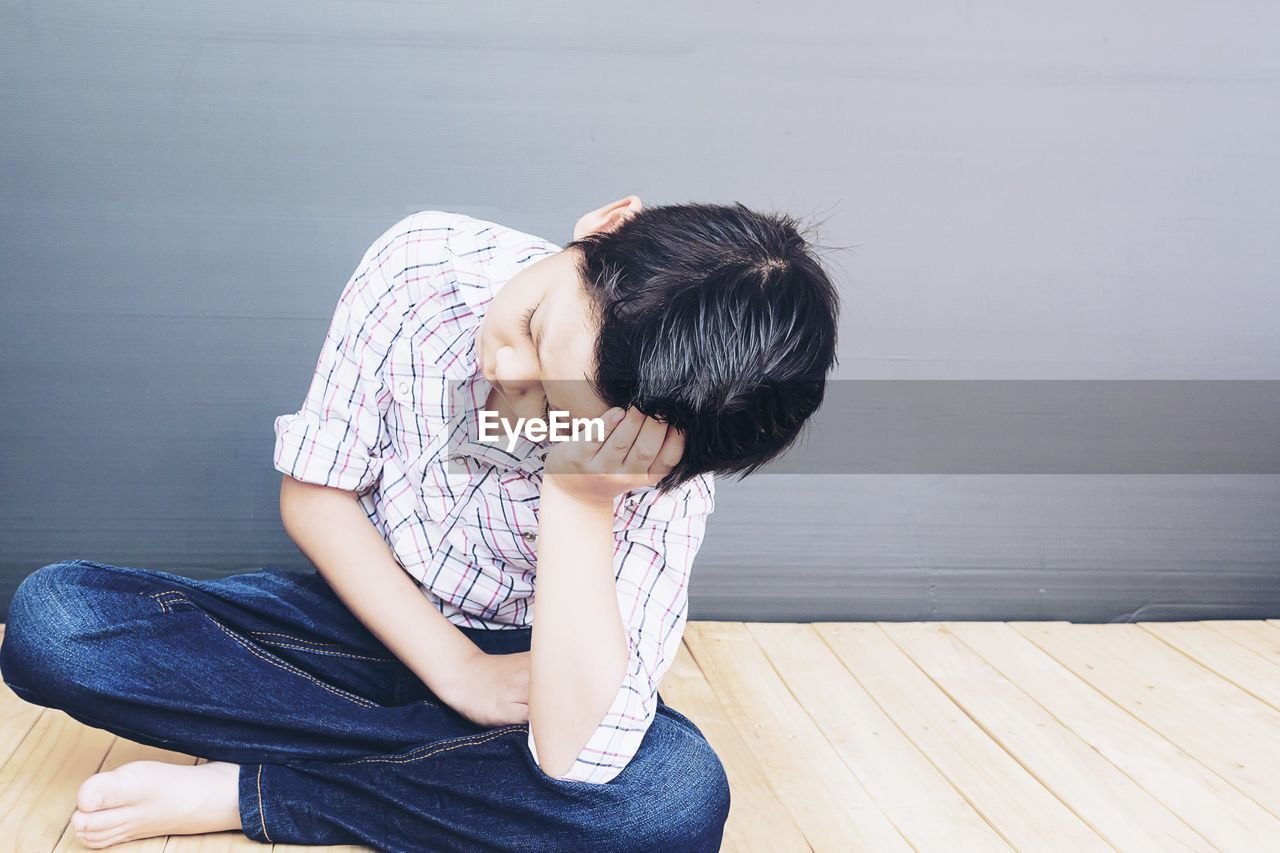 one person, real people, casual clothing, sitting, three quarter length, black hair, lifestyles, women, young adult, leisure activity, sadness, hair, indoors, young women, adult, wall - building feature, emotion, depression - sadness, flooring, hairstyle, obscured face, jeans