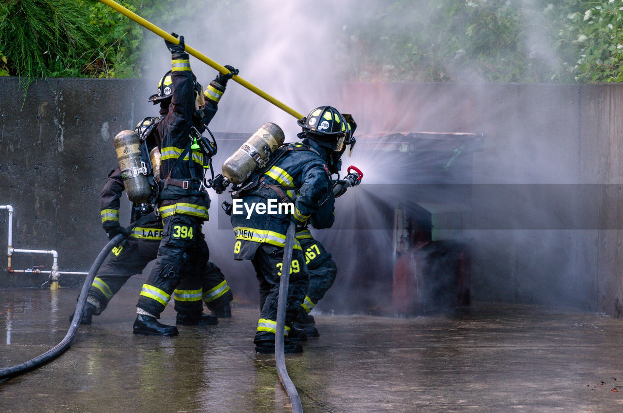 Rear View Of Firefighter Using Water Hose