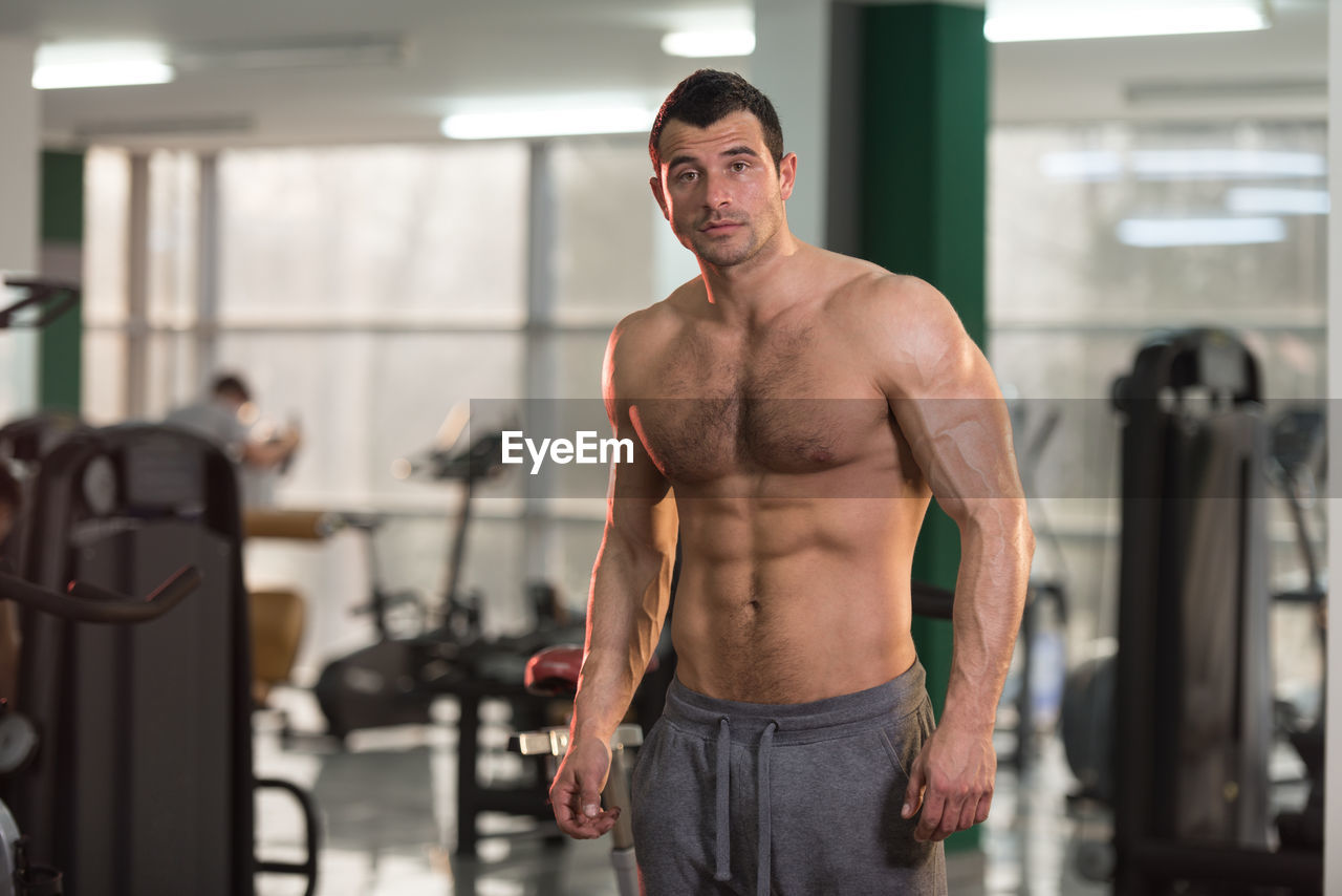 Portrait of shirtless man standing in gym