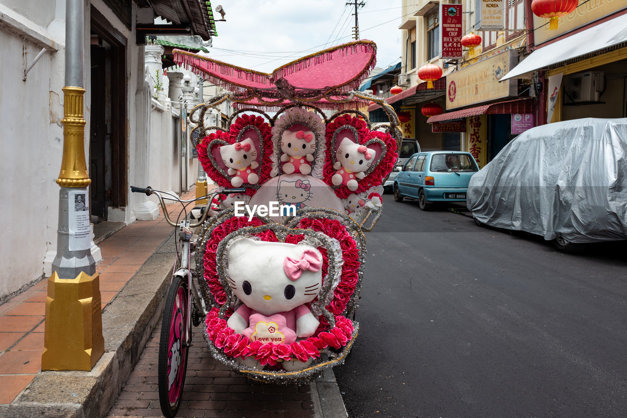 representation, architecture, day, city, animal representation, no people, creativity, art and craft, toy, street, built structure, building exterior, pink color, outdoors, transportation, stuffed toy, animal themes, land vehicle, mode of transportation