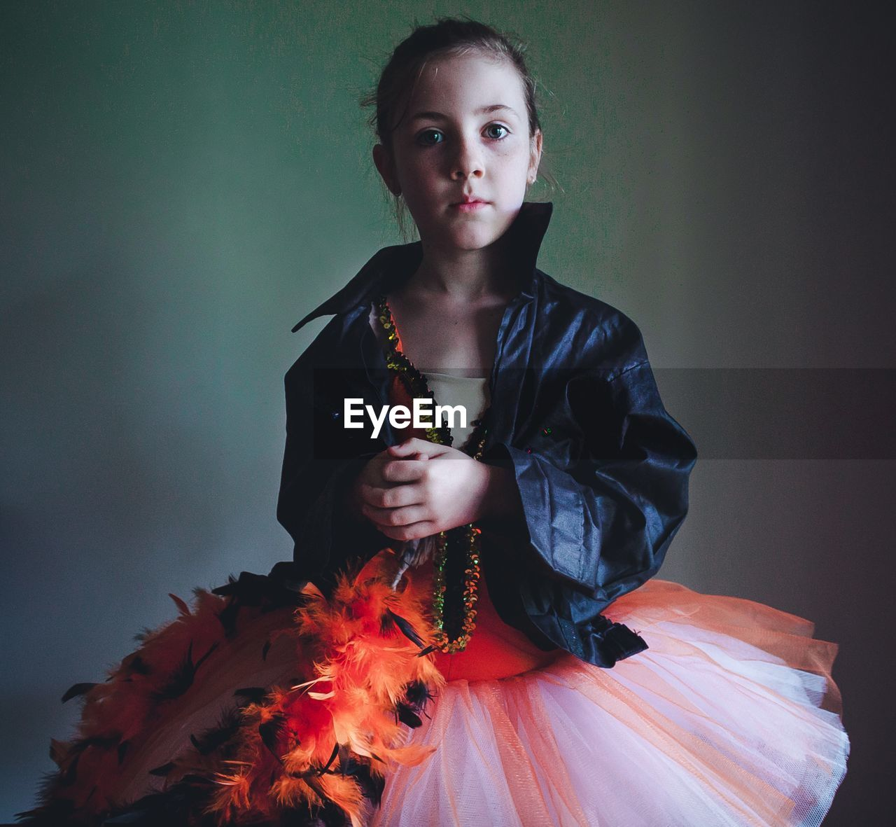 Portrait Of Confident Girl Wearing Tutu And Jacket Against Wall
