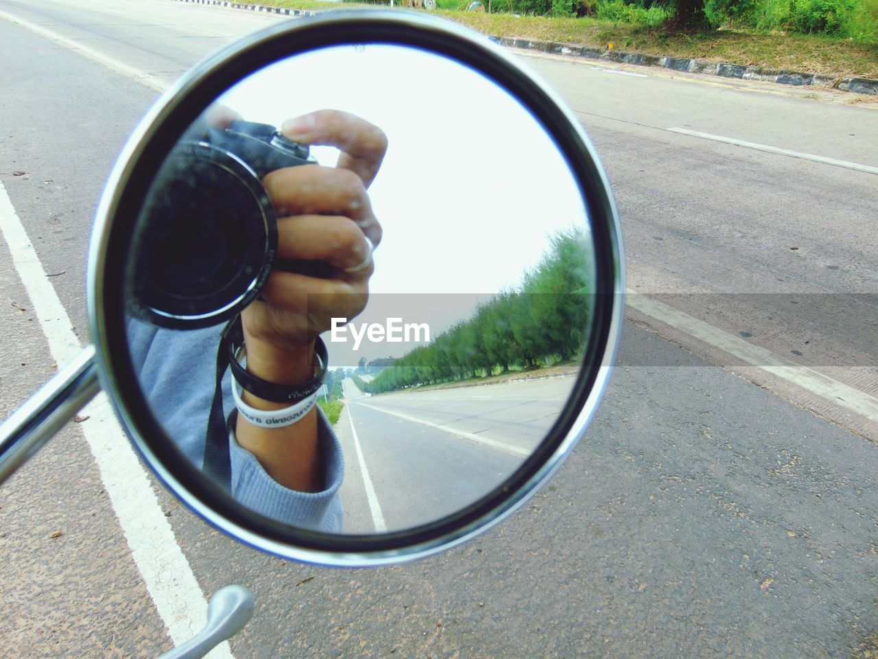 CLOSE-UP OF HAND ON SIDE-VIEW MIRROR OF CAR