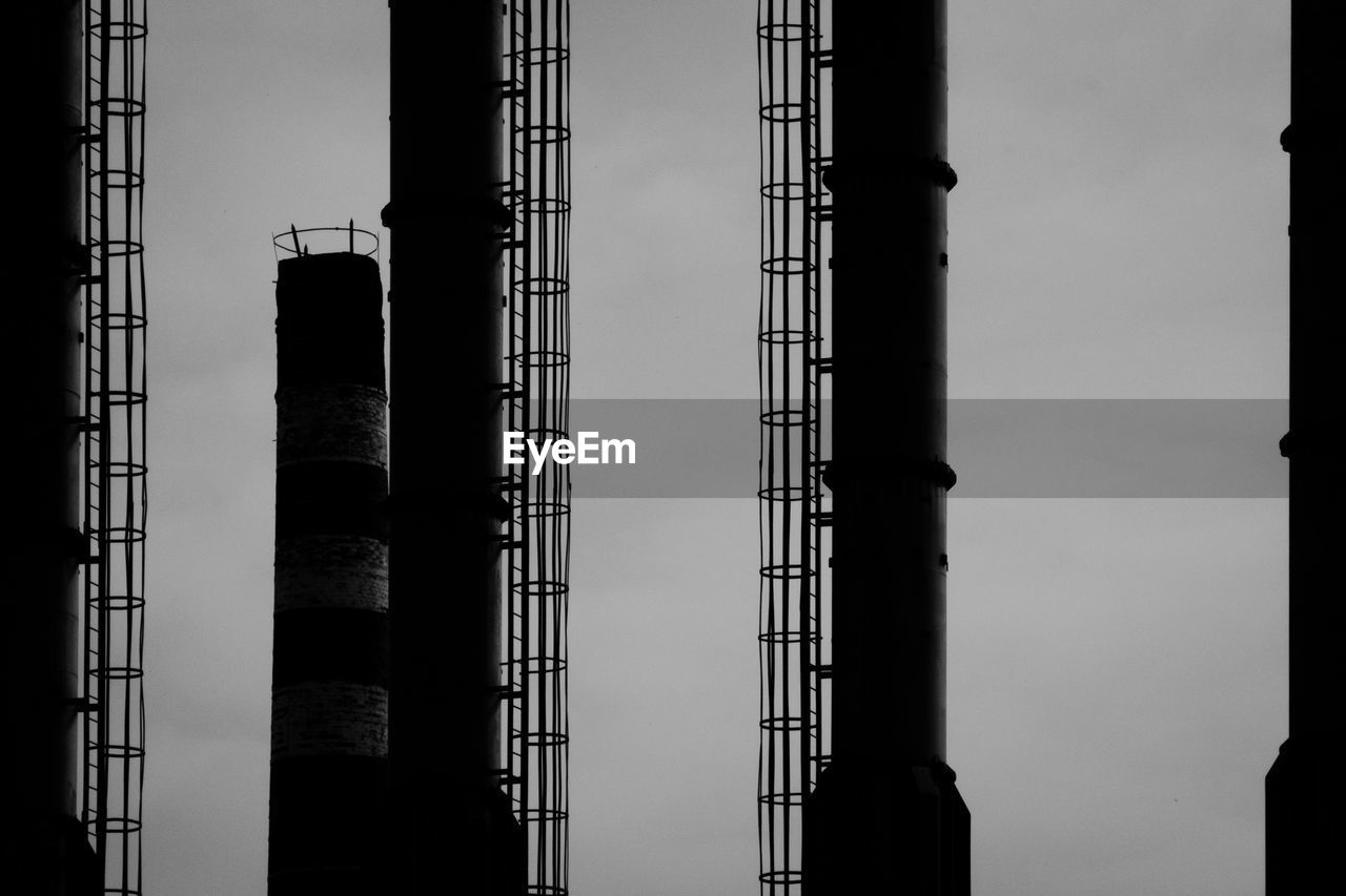 architecture, built structure, sky, industry, fuel and power generation, no people, low angle view, building exterior, factory, metal, nature, day, outdoors, development, tall - high, smoke stack, silhouette, environmental issues, construction industry, dusk, power supply