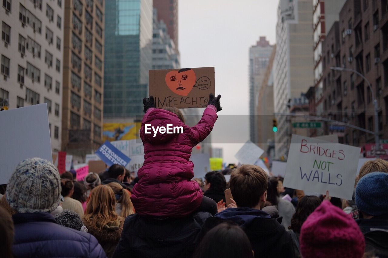 text, protest, communication, protestor, real people, placard, heart shape, architecture, anger, women, day, holding, men, banner - sign, built structure, building exterior, outdoors, city, lifestyles, large group of people, riot, adult, people