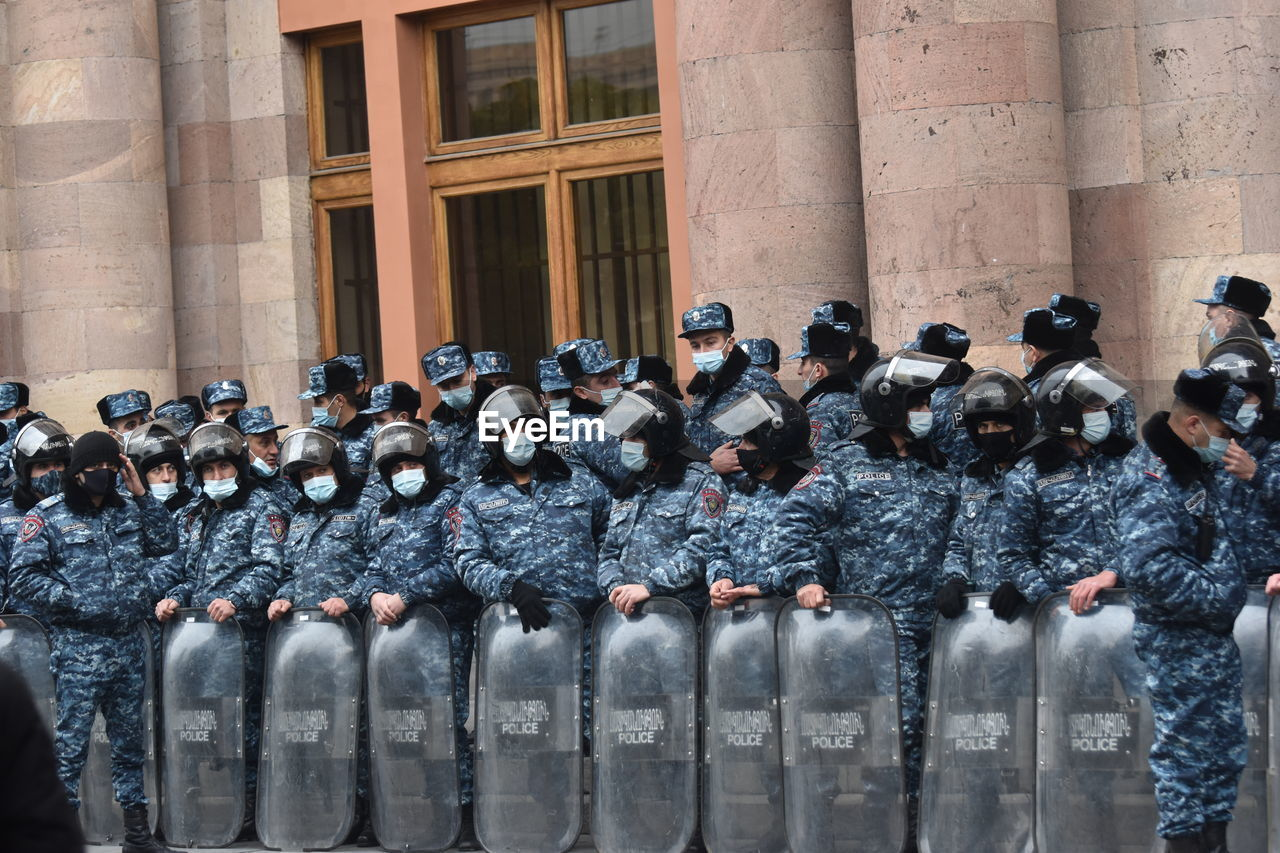 Police in riot gear protecting the government building against protestors