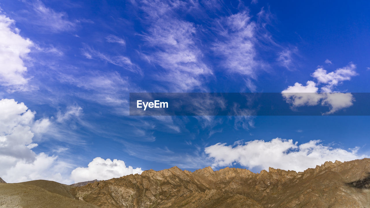 sky, cloud - sky, beauty in nature, scenics - nature, blue, tranquility, tranquil scene, mountain, nature, non-urban scene, day, rock, no people, rock - object, low angle view, landscape, environment, idyllic, remote, solid, outdoors, arid climate, climate