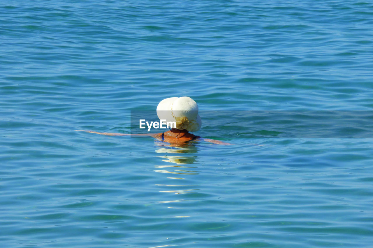 High Angle View Of Woman Wearing Hat Swimming In Sea