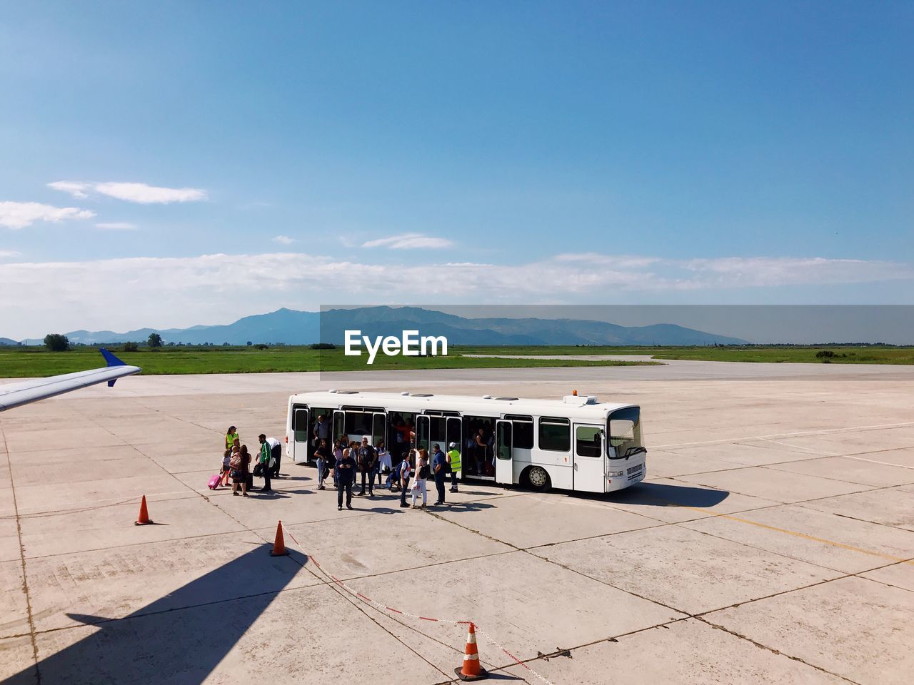 sky, group of people, real people, day, sunlight, airplane, nature, air vehicle, men, transportation, mode of transportation, airport, airport runway, travel, lifestyles, women, large group of people, cloud - sky, leisure activity, outdoors, aerospace industry