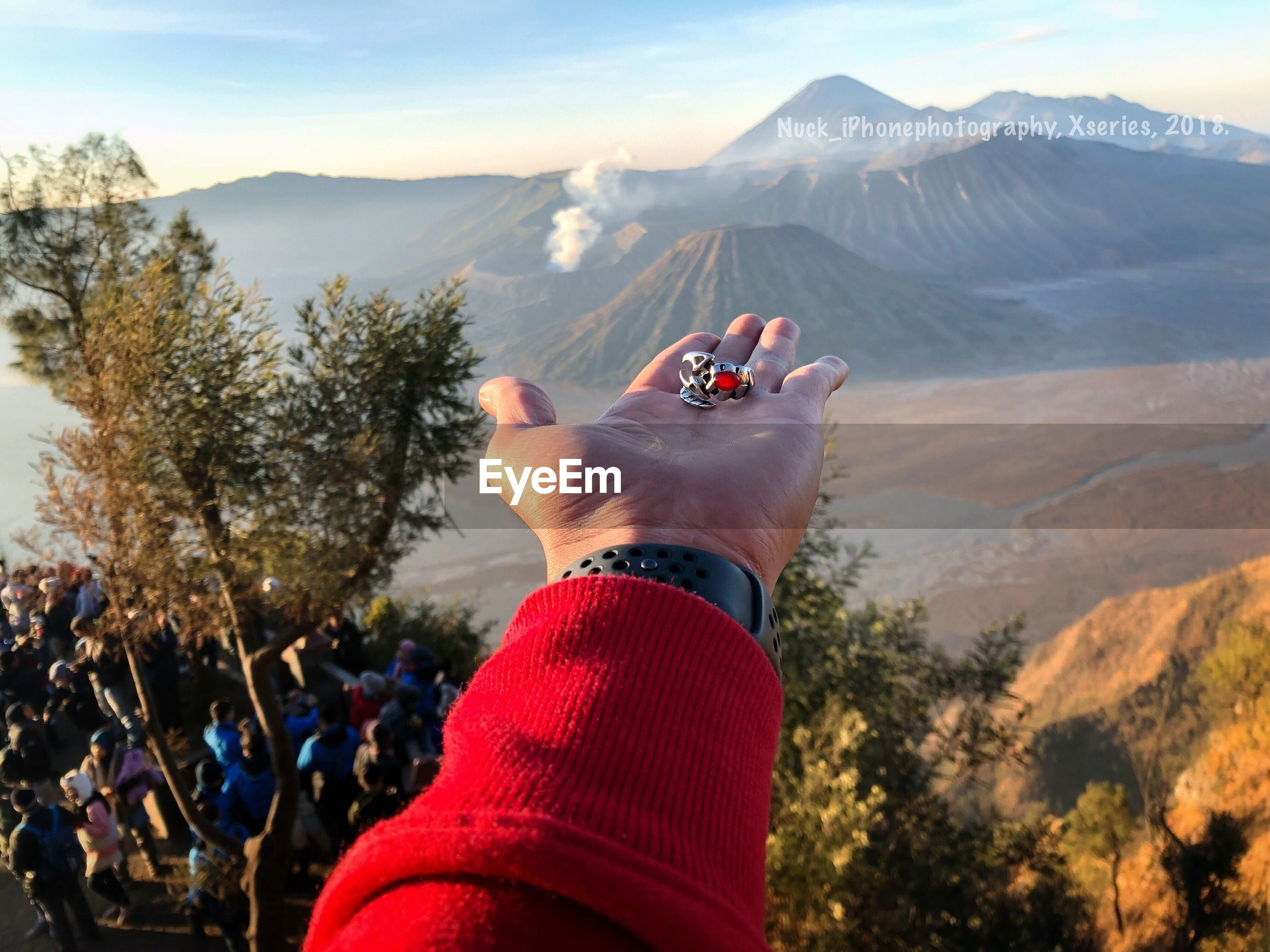 Cropped image of hand holding ring against mountains during foggy weather