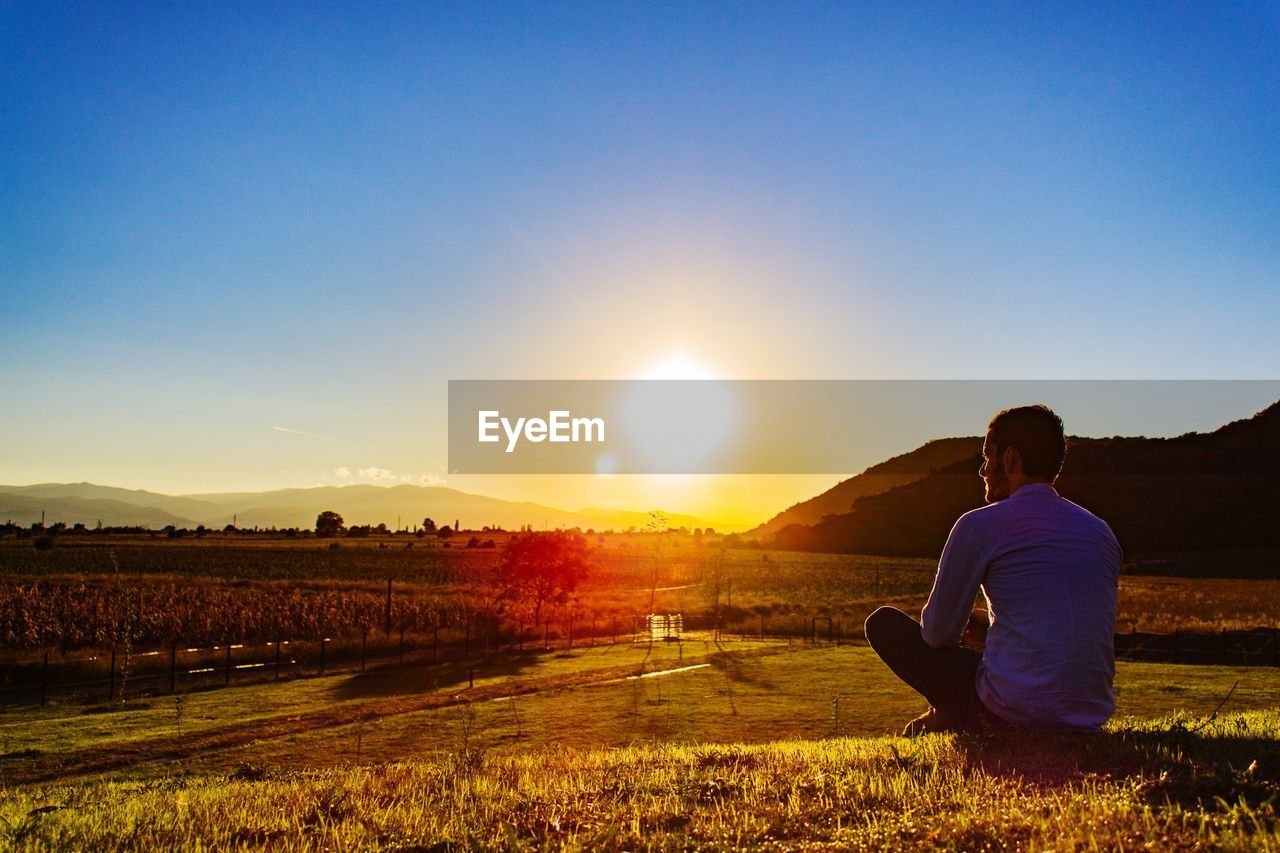 Man Sitting On Agricultural Field Against Clear Sky During Sunset