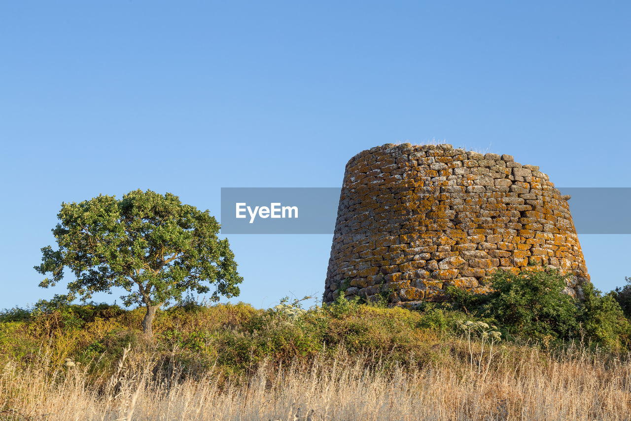 Low angle view of old ruin on field against clear sky