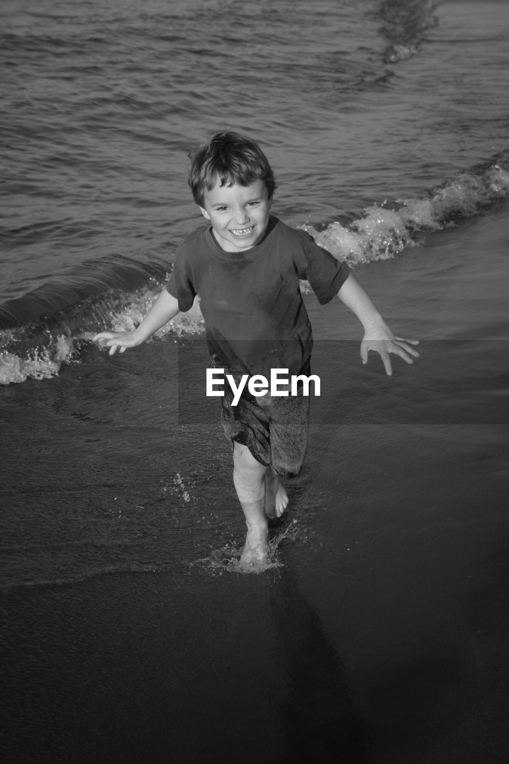 Portrait of cheerful boy at sea