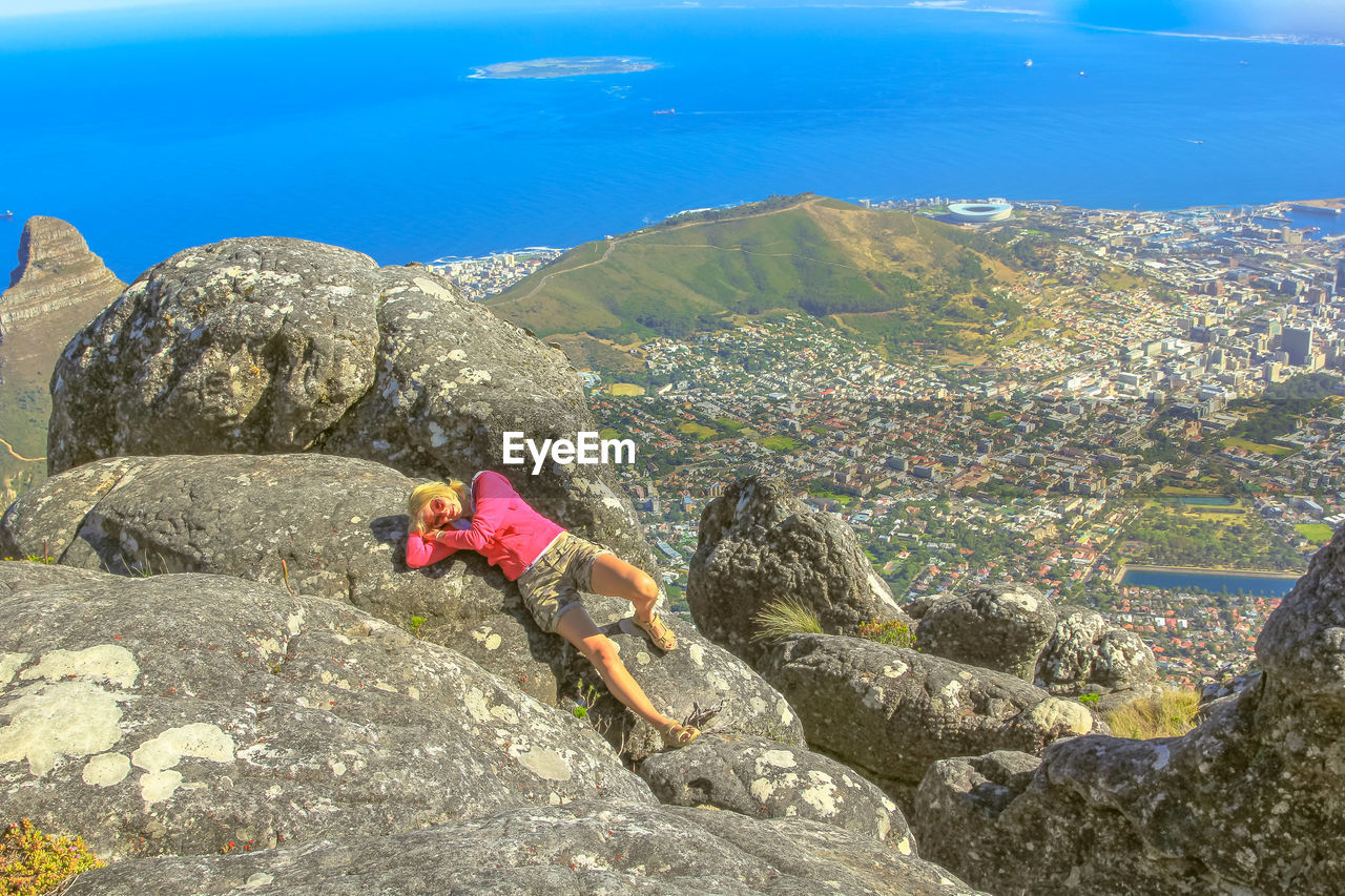 Portrait of mature woman lying on mountain against cityscape