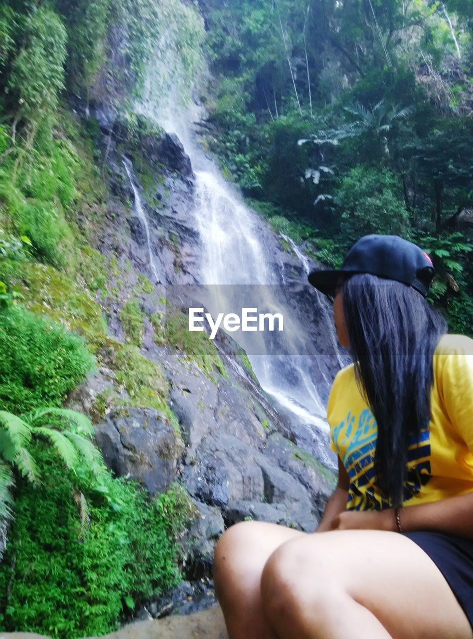 waterfall, real people, rock - object, one person, motion, outdoors, rear view, day, water, nature, beauty in nature, lifestyles, women, leisure activity, long exposure, scenics, sitting, standing, mountain, tree, young adult, people, adult