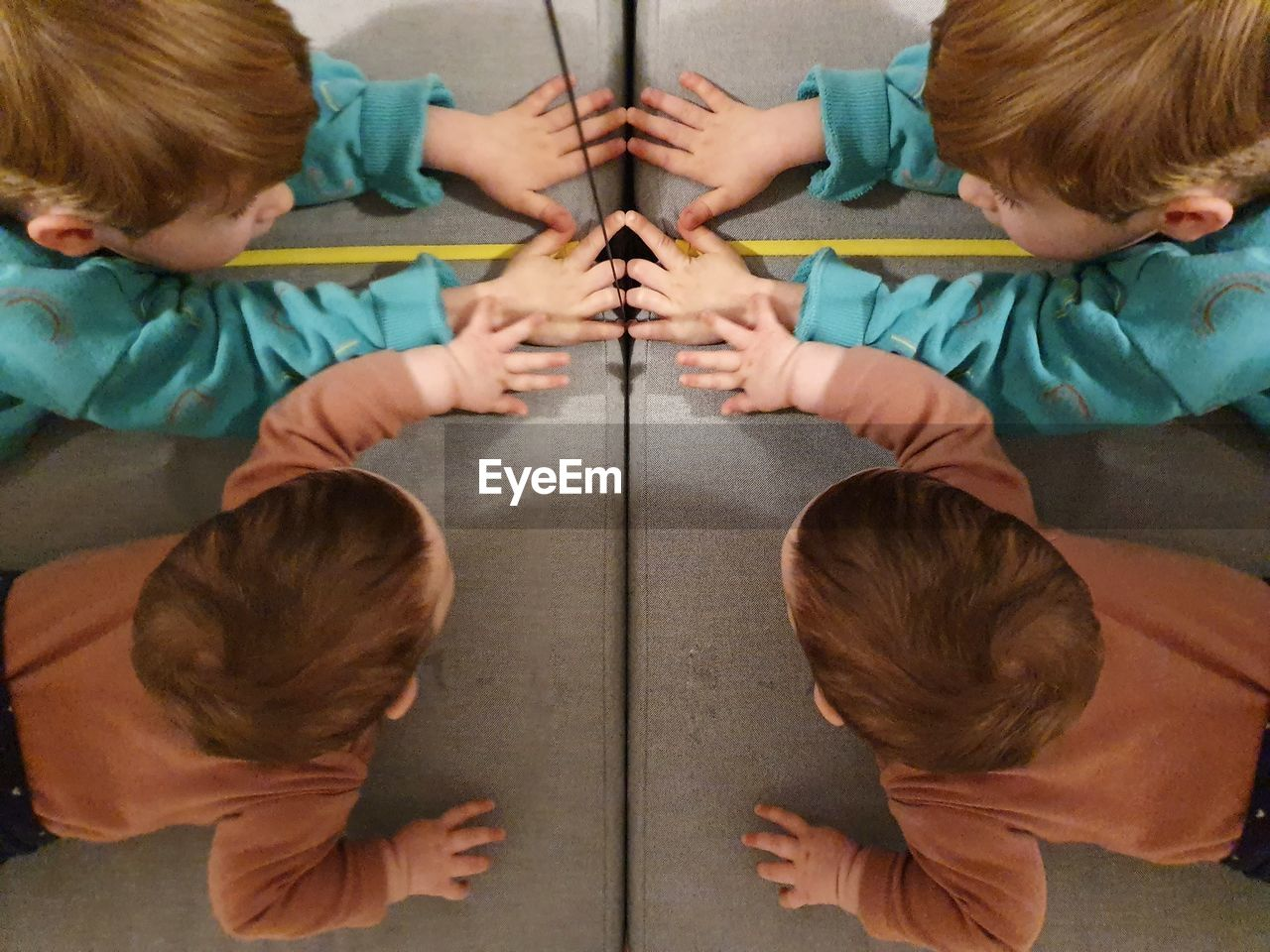 High angle view of siblings reflecting on glass