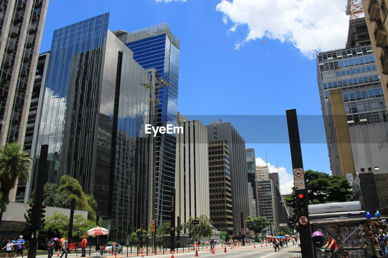 architecture, building exterior, built structure, city, skyscraper, real people, outdoors, modern, city life, sky, day, tree, large group of people, women, men, people