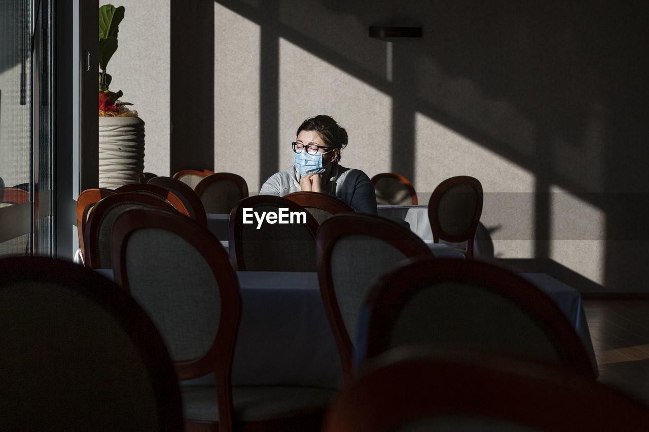 Woman wearing mask sitting at cafe