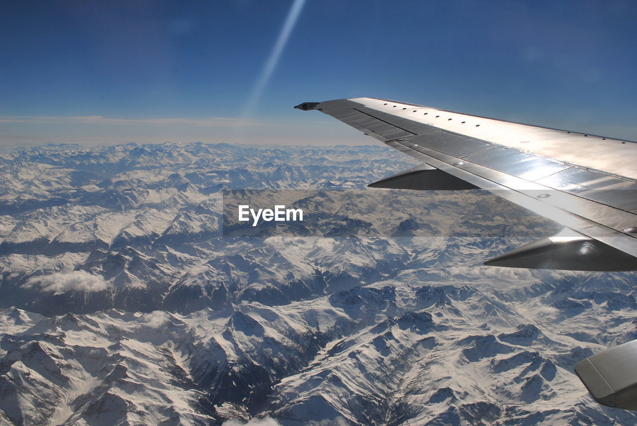 Airplane flying over snowy mountain range