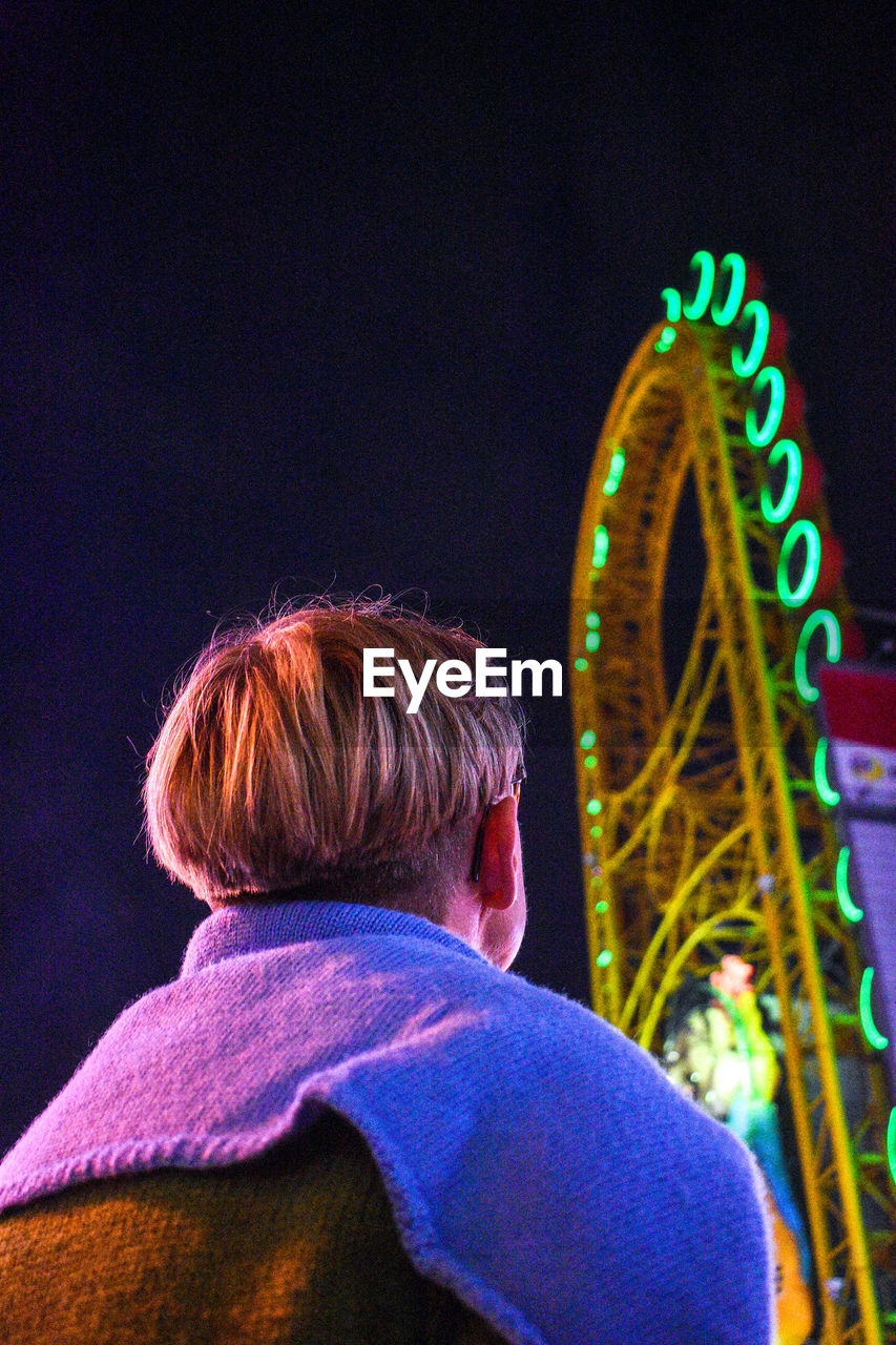 Low Angle View Of Man Standing Against Illuminated Amusement Park Ride At Night