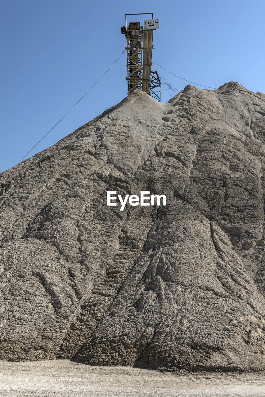 sky, nature, clear sky, rock, no people, day, solid, architecture, land, built structure, rock - object, low angle view, outdoors, mountain, connection, cable, technology, blue, building exterior, electricity