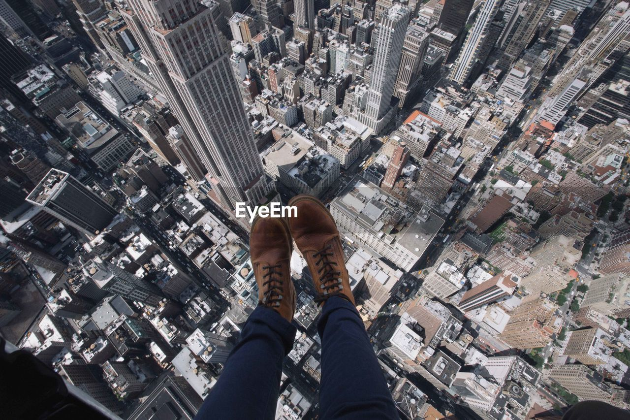 city, cityscape, human body part, one person, architecture, office building exterior, low section, high angle view, skyscraper, building, aerial view, body part, building exterior, built structure, shoe, tower, crowded, personal perspective, transportation, outdoors, modern, human foot