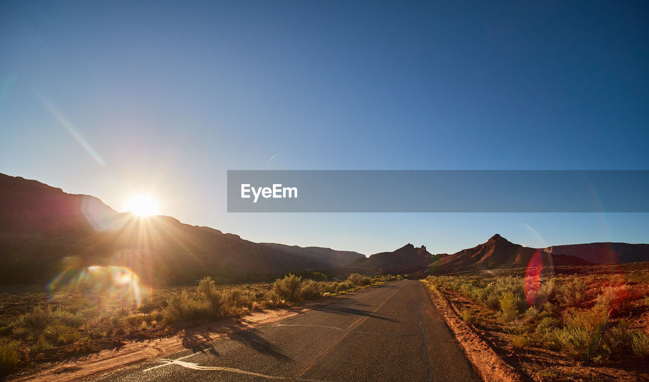 sky, road, sunlight, mountain, nature, transportation, direction, clear sky, the way forward, copy space, sun, beauty in nature, tranquility, sunbeam, tranquil scene, blue, landscape, environment, scenics - nature, no people, lens flare, mountain range, diminishing perspective, bright, long, brightly lit