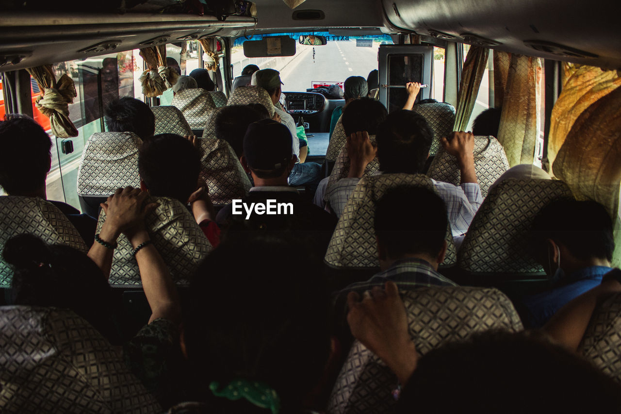 group of people, real people, crowd, large group of people, vehicle interior, rear view, women, transportation, men, adult, public transportation, lifestyles, travel, mode of transportation, journey, land vehicle, passenger, sitting, bus, nightlife