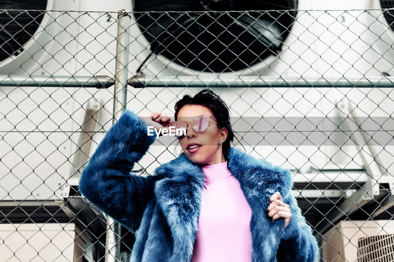 one person, real people, leisure activity, lifestyles, front view, fence, winter, young adult, smiling, clothing, portrait, warm clothing, women, chainlink fence, happiness, emotion, coat, fur, fur coat, beautiful woman, outdoors