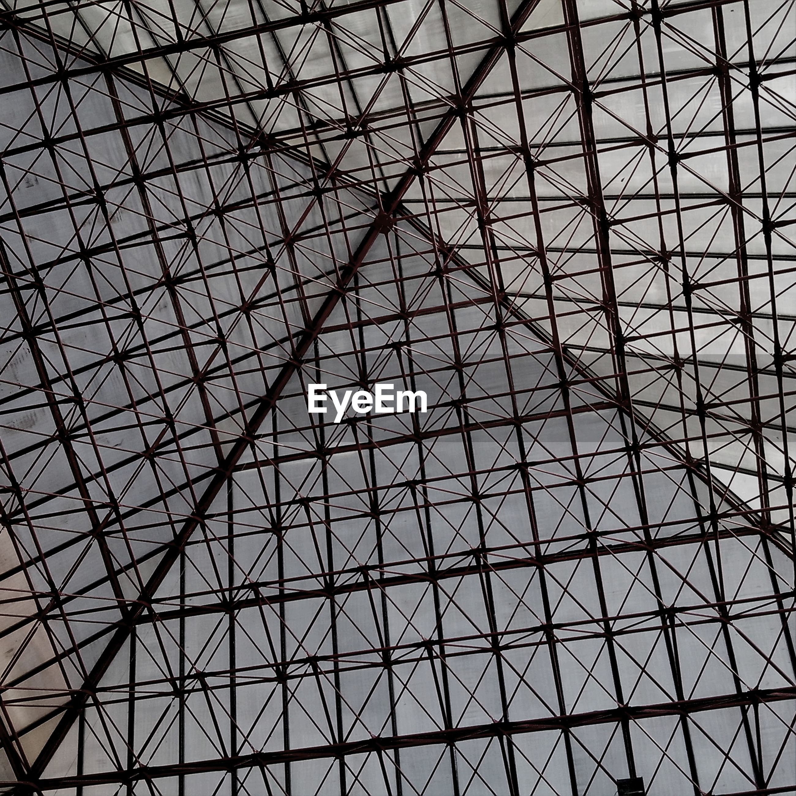 low angle view, ceiling, built structure, architecture, pattern, architectural feature, full frame, design, indoors, backgrounds, directly below, glass - material, sky, modern, skylight, grid, day, metal, geometric shape, no people