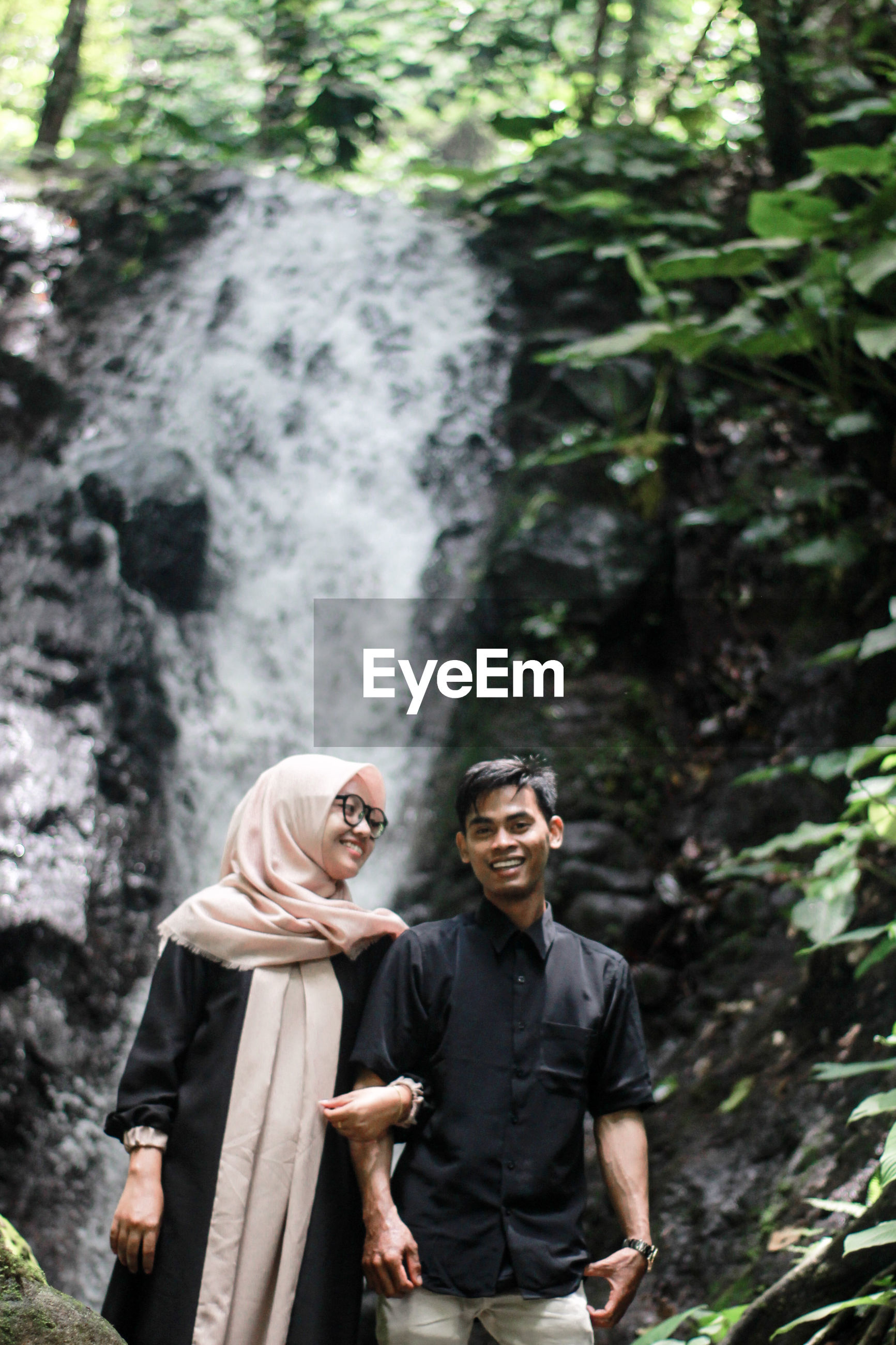 Young couple standing against waterfall at forest