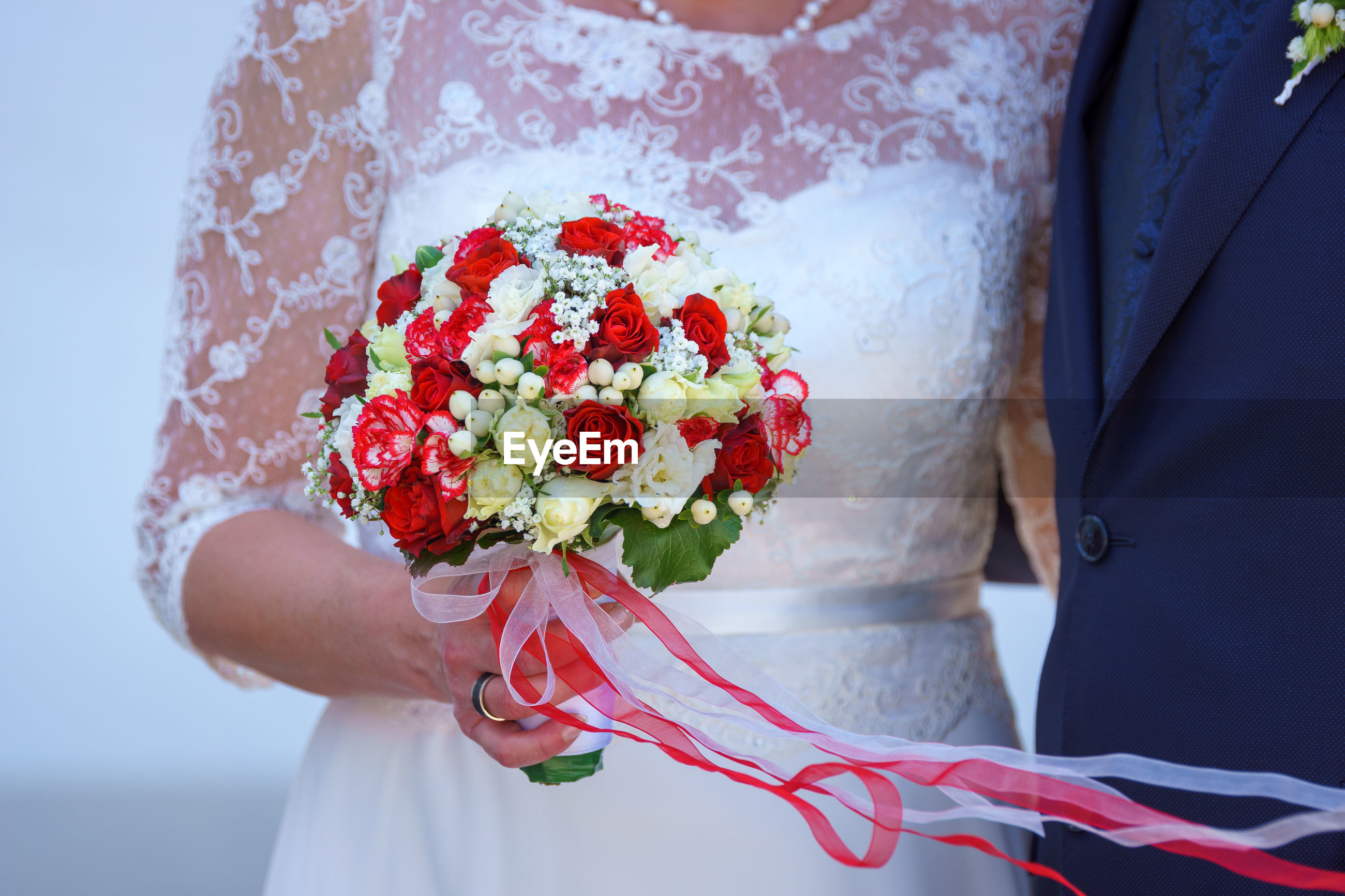 CLOSE-UP OF WOMAN HOLDING BOUQUET OF RED ROSE