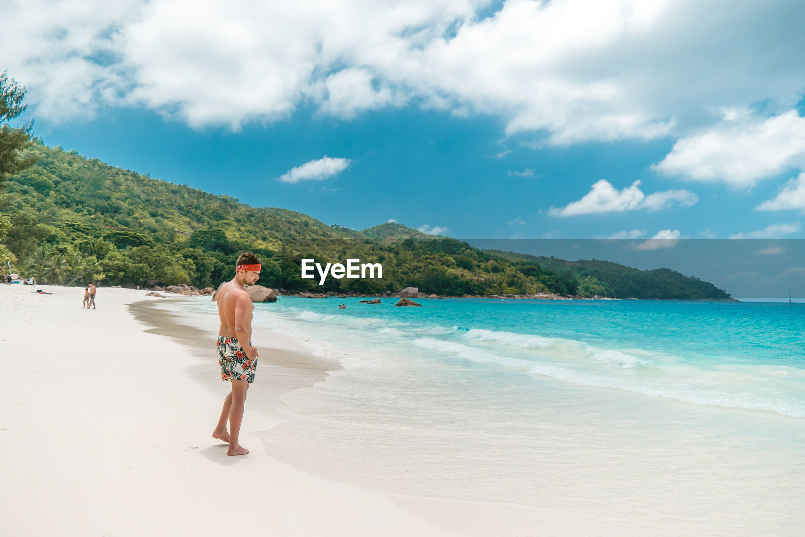 Shirtless mid adult man standing at beach against cloudy sky