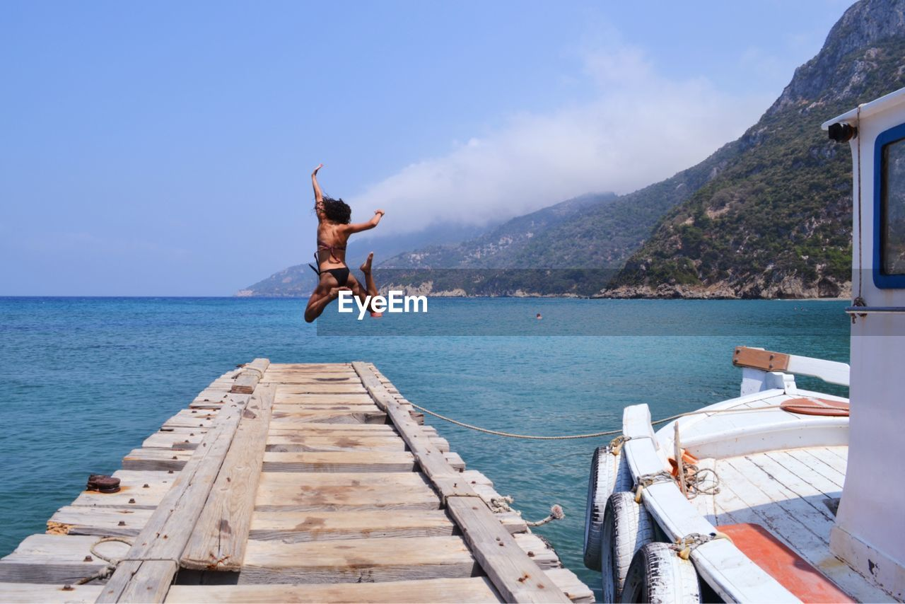 Woman jumping on pier over sea against sky
