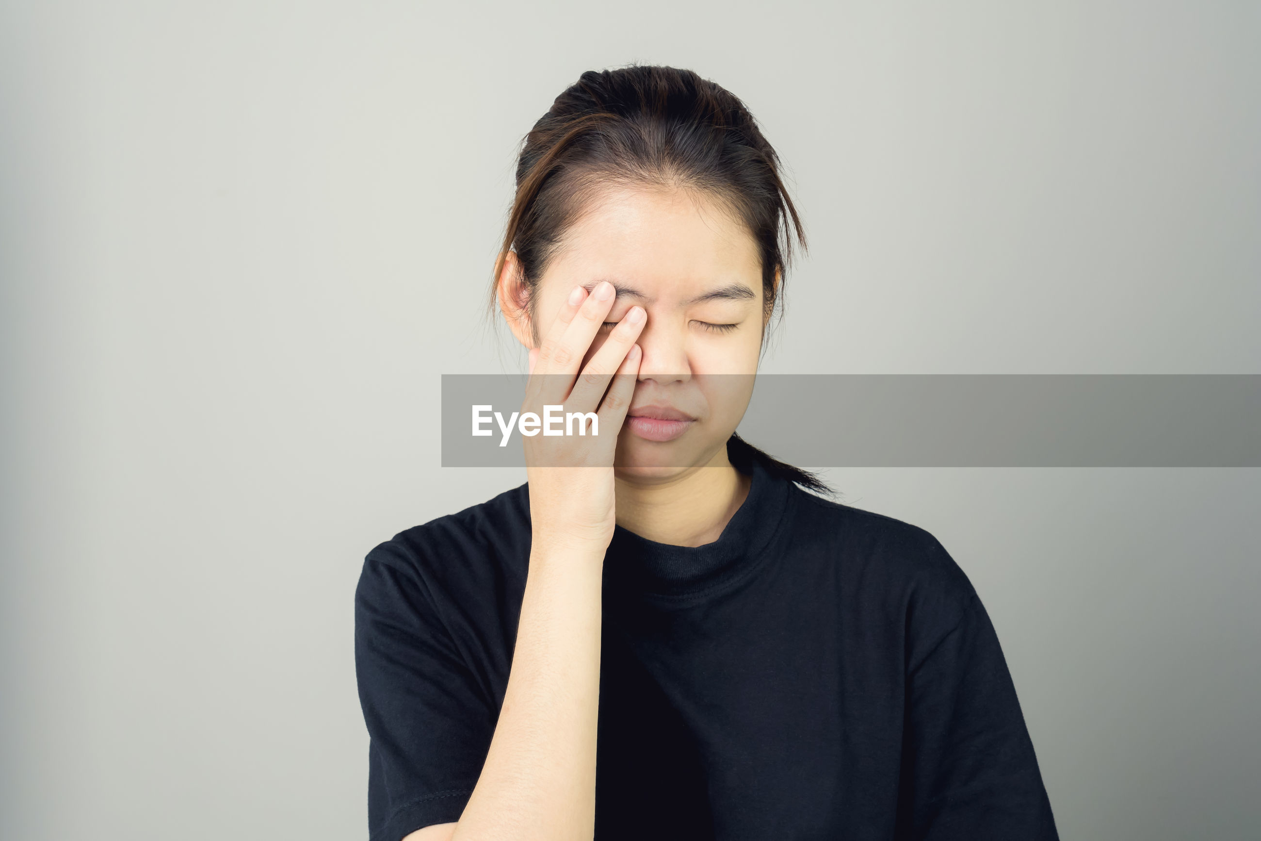 Close-up of tired young woman standing against gray background