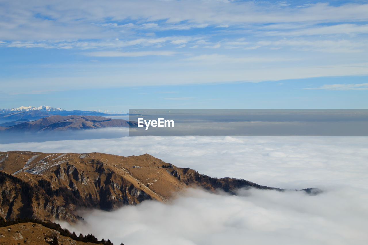 Scenic view of mountains against sky in foggy weather