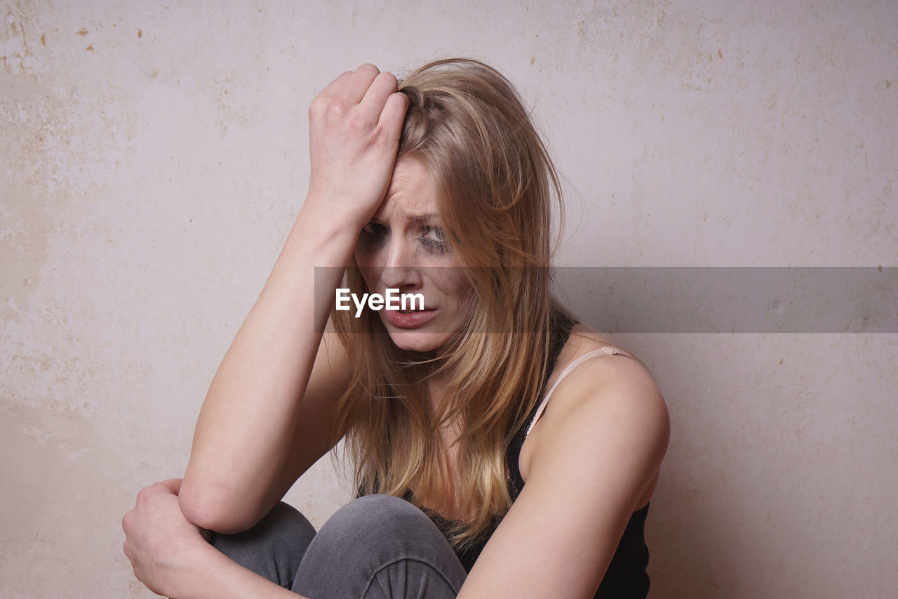 Portrait Of Crying Young Woman Sitting Against Wall