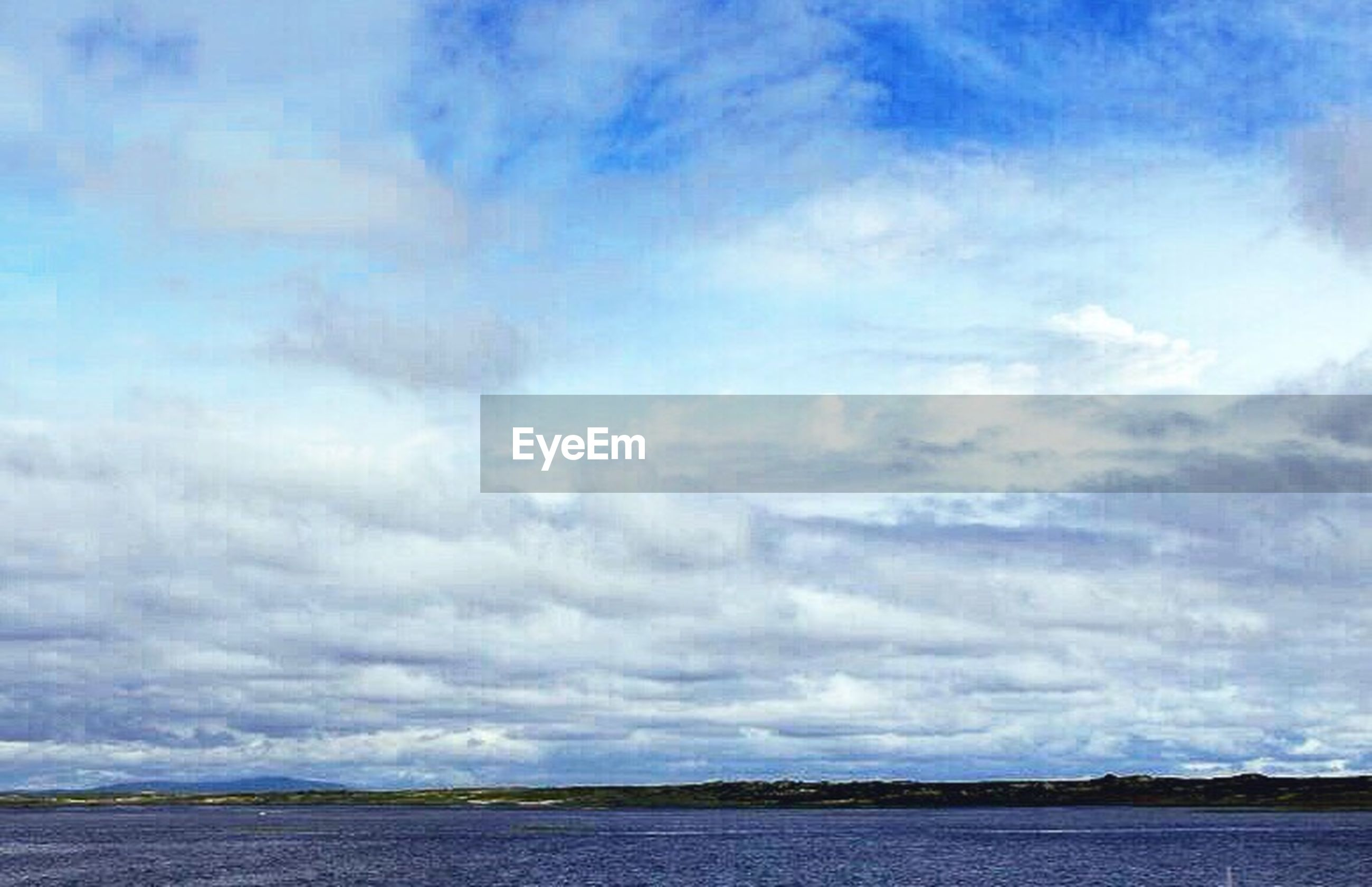sky, tranquil scene, tranquility, scenics, water, beauty in nature, cloud - sky, waterfront, sea, nature, cloudy, cloud, blue, idyllic, day, weather, landscape, outdoors, non-urban scene, remote