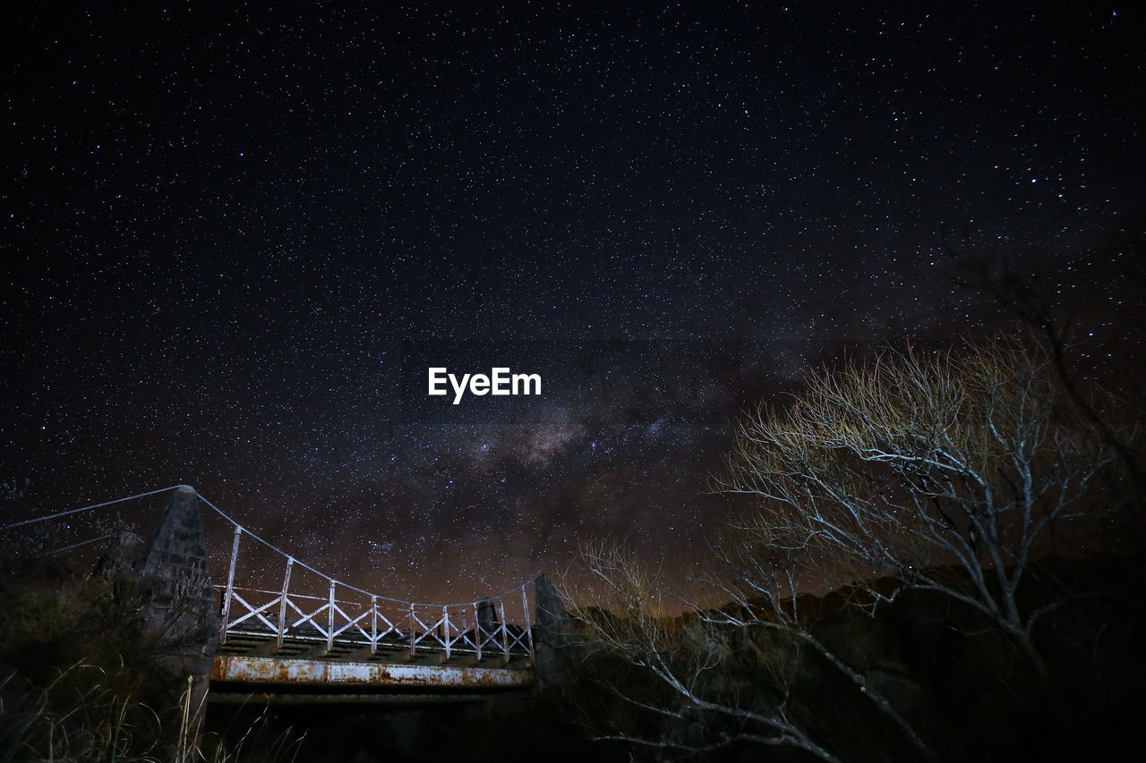 Low Angle View Of Old Bridge By Bare Trees Against Milky Way